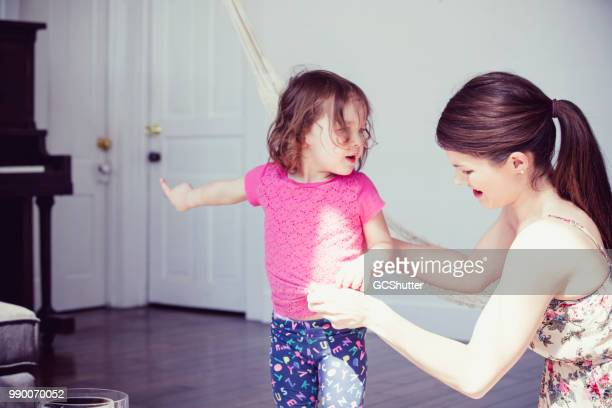 Mother trying to dress her daughter while baby girl wants to play piano