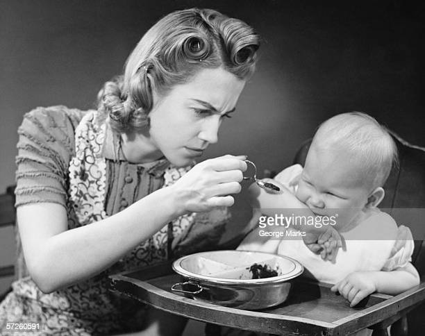 Mother trying to feed unwilling baby (9-12 months), (B&W)