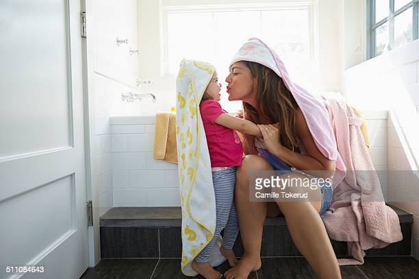Mother trying to kiss little girl