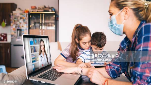mother trying to talk with doctor on laptop while watching two kids - telemedicine stock pictures, royalty-free photos & images