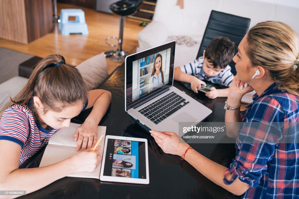 Moeder die met arts op laptop probeert te spreken terwijl het letten op twee jonge geitjes die thuis blijven Homeschooling en afstandsleren : Stockfoto