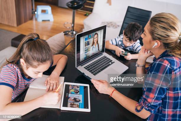 mother trying to talk with doctor on laptop while watching two kids staying home homeschooling and distance learning - equipment stock pictures, royalty-free photos & images