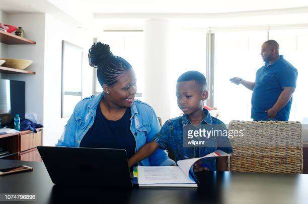 mother trying to work with son interfering and father with remote - tv housewife stock photos and pictures
