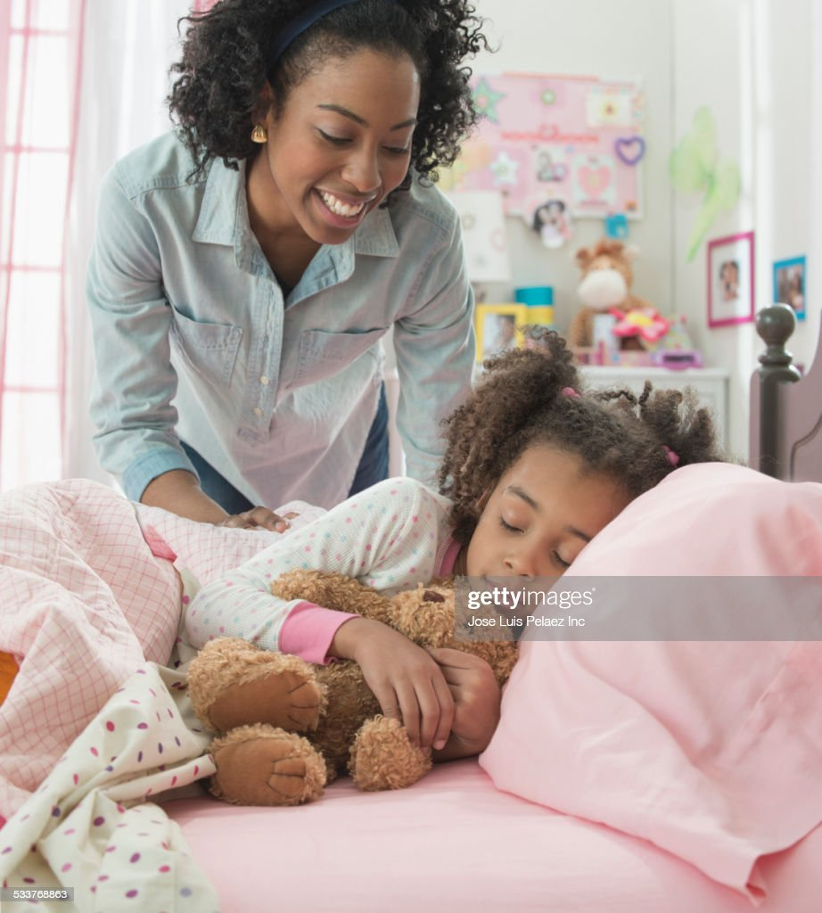 Mother tucking daughter into bed : Foto stock