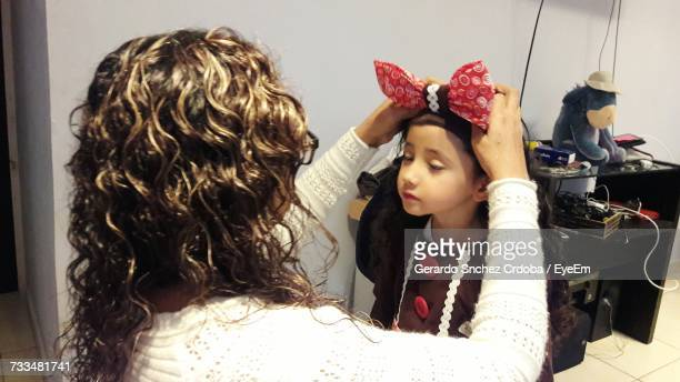 mother tying bow on daughter hair at home - hair bow stock pictures, royalty-free photos & images