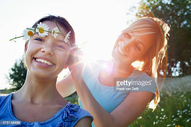 Mother tying daisy chain around daughter's head