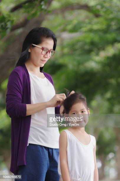Mother Tying Daughter Hair While Standing Against Tree