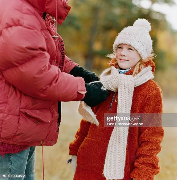 mother tying daughter's scarf - sciarpa foto e immagini stock