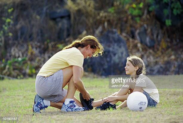 Mother tying daughter's (10-12 years) shoes outdoors with soccer ball,