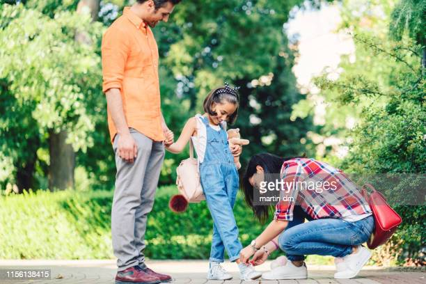 mother tying shoelaces of her daughter in the park - school girl shoes stock pictures, royalty-free photos & images