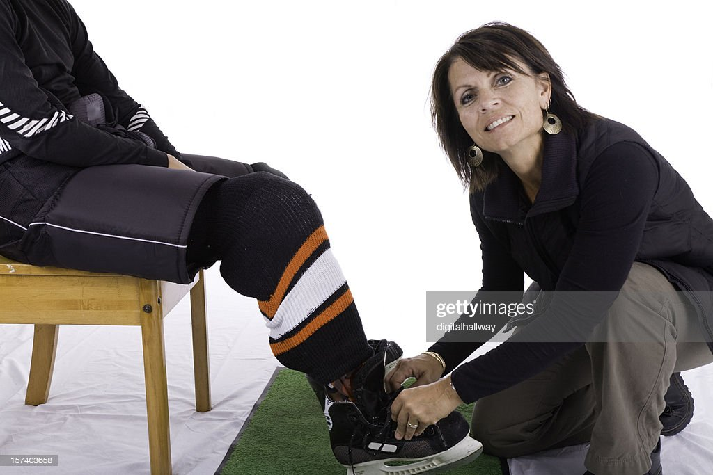 Mother tying sons hockey skates : Stock Photo