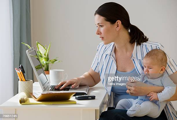 Mother typing on laptop and holding baby