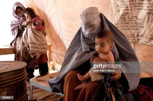 A mother undresses her child by the heater at the Medecins Sans Frontieres clinic November 23 2003 in Bamiyan Afghanistan MSF provides free health...