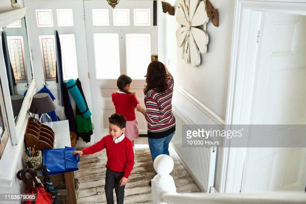 mother unlocking front door as son and daughter leave for school - philippine independence day stock pictures, royalty-free photos & images