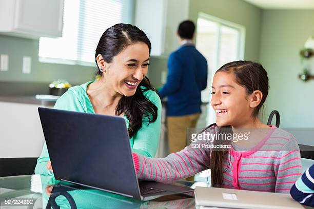 Mother uses laptop as she homeschools daughter