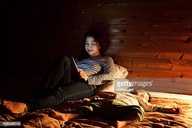 Mother using a digital tablet on the bed at night