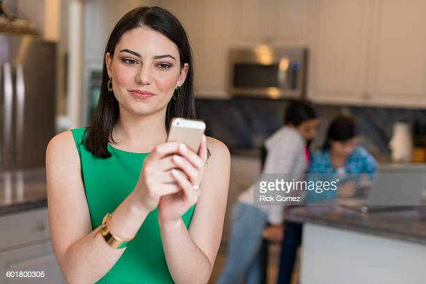Mother using cell phone in kitchen