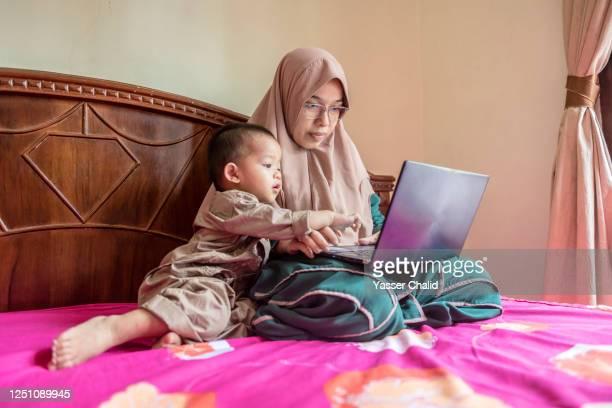 Mother using laptop in bedroom