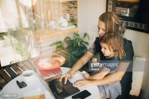 mother using laptop while daughter sitting on lap seen through glass window - working from home stock pictures, royalty-free photos & images