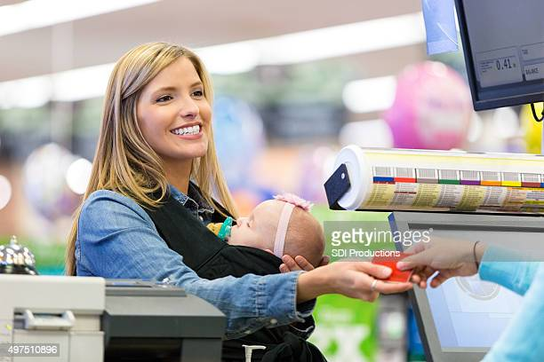 Mother using loyalty card or credit card in grocery store