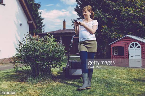 Mother using mobile phone in garden.