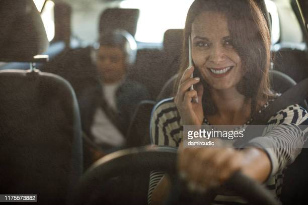 mother using mobile phone while driving a car - damircudic stock photos and pictures