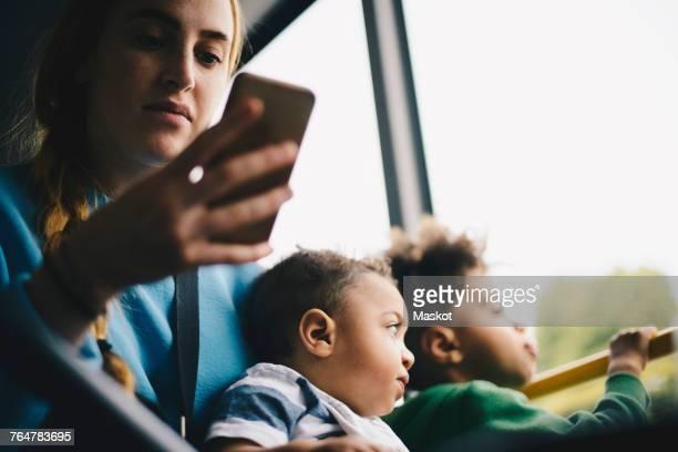 mother using mobile phone while sitting with son in bus - alleenstaande moeder stockfoto's en -beelden