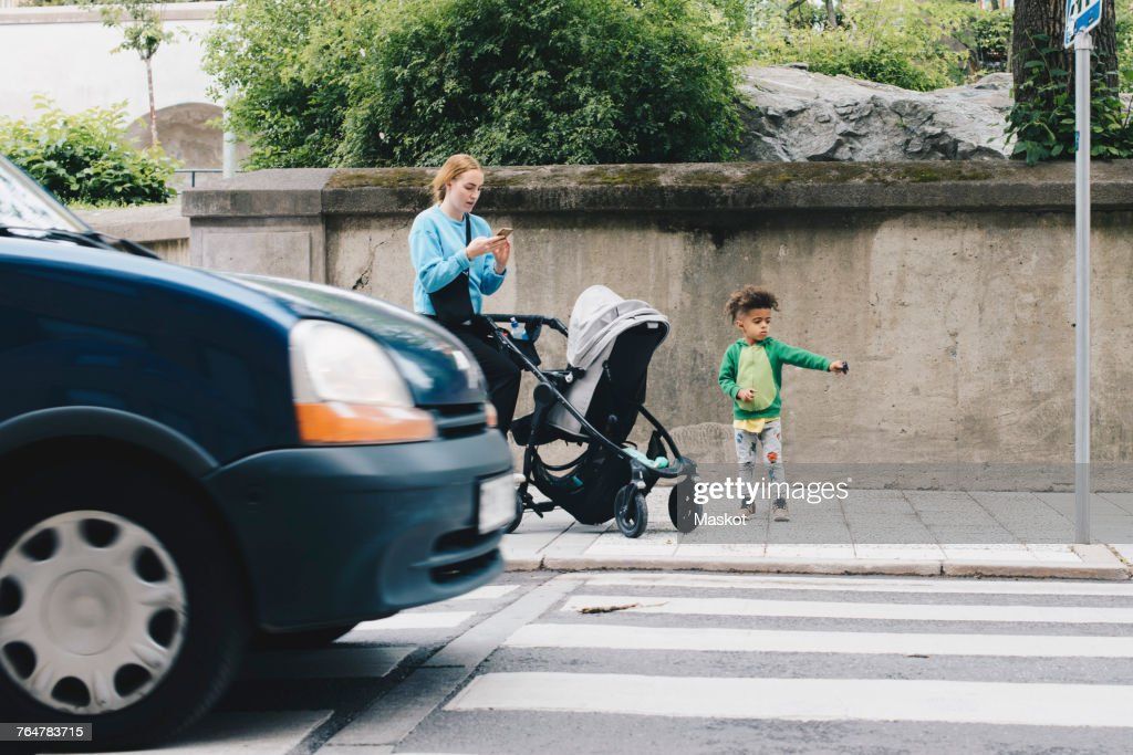 Mother using mobile phone while standing with son and baby stroller on sidewalk at city : Stock Photo
