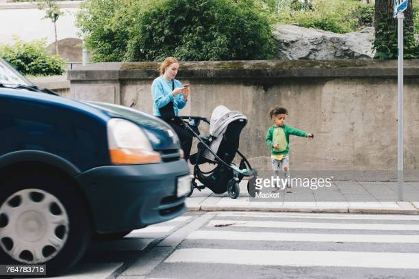 mother using mobile phone while standing with son and baby stroller on sidewalk at city - zebra crossing stock pictures, royalty-free photos & images