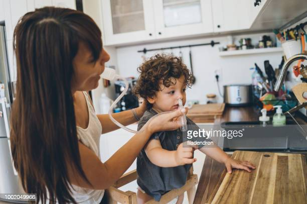 Mother using nasal aspirator for her son