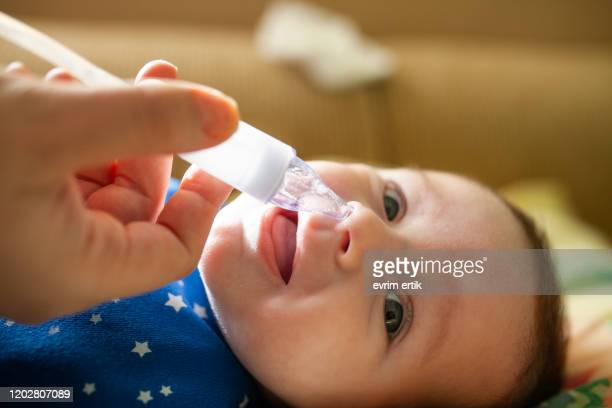 mother using nasal aspirator for her son stock photo - mucus stock pictures, royalty-free photos & images