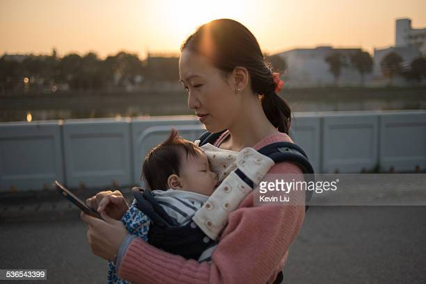 Mother using phone while carrying sleeping baby