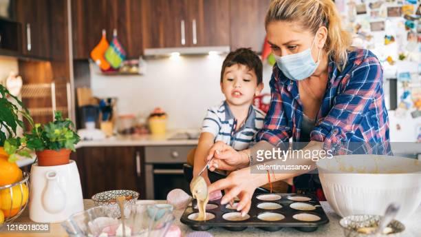 mère utilisant le masque protecteur faisant des petits gâteaux délicieux avec ses enfants isolement à la maison pour le virus - confinement photos et images de collection