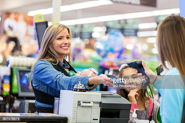 mother using smart phone to pay for purchases in store - cash register stock pictures, royalty-free photos & images
