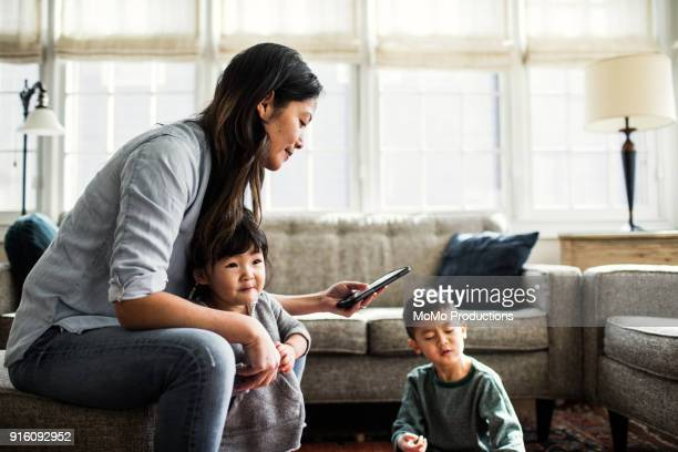 Mother using smartphone with children present