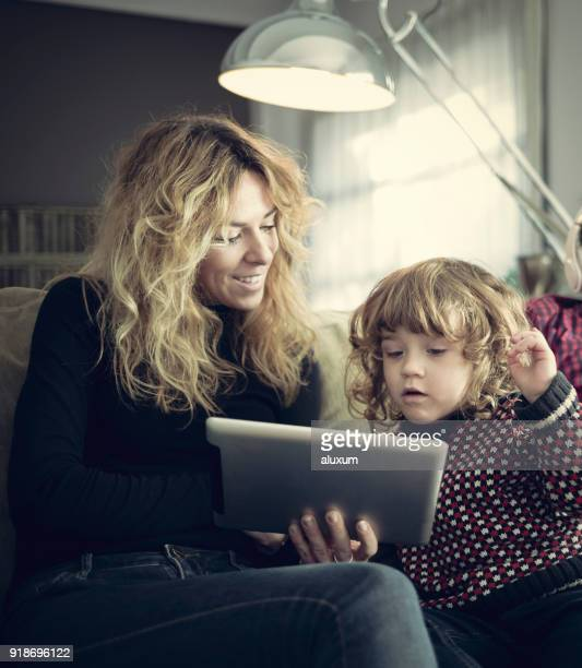mother using tablet with her son at home - free business coaching stock pictures, royalty-free photos & images