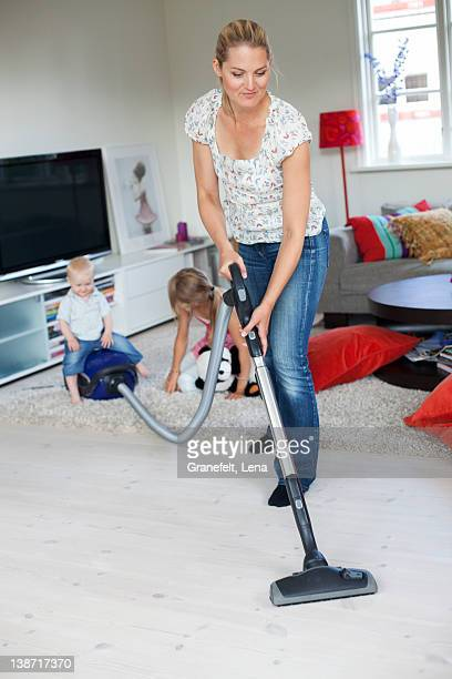 Mother vaccuming with her daughters playing in the background