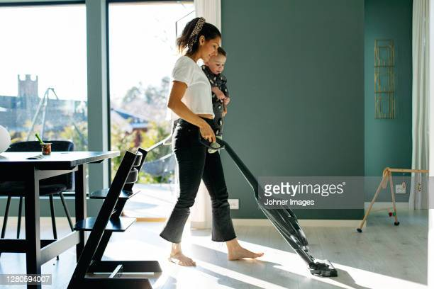 mother vacuum cleaning while carrying toddler son - housework stock pictures, royalty-free photos & images