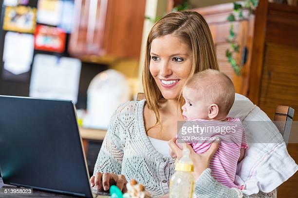 Mutter video-Chats von home office und hält baby Tochter