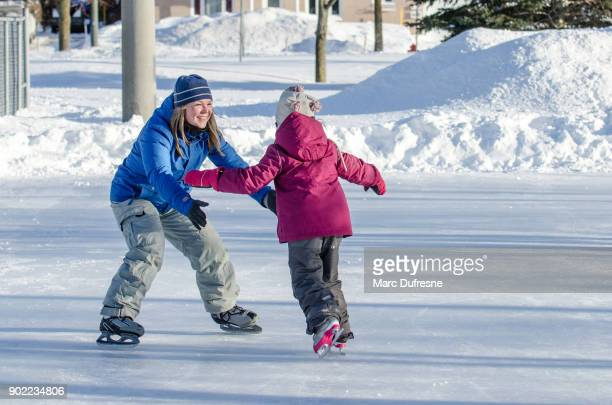 mother waiting with arms opened her daughter  to help her ice skating - skating stock pictures, royalty-free photos & images