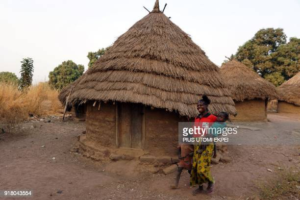 A mother walk past mud house walks in front of mud house with her children in Tse Chagu on the outskirts of Makurdi capital of Benue State in...