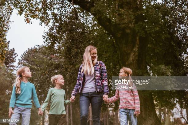 Mother walking and talking with her children in public park
