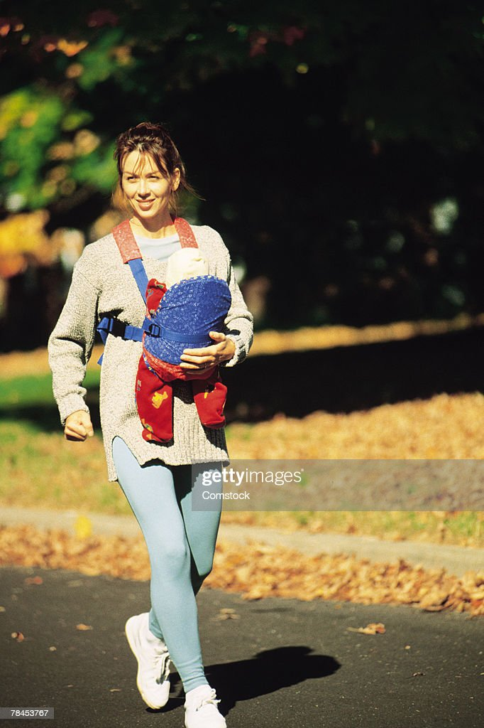 Mother walking briskly while carrying baby : Stockfoto