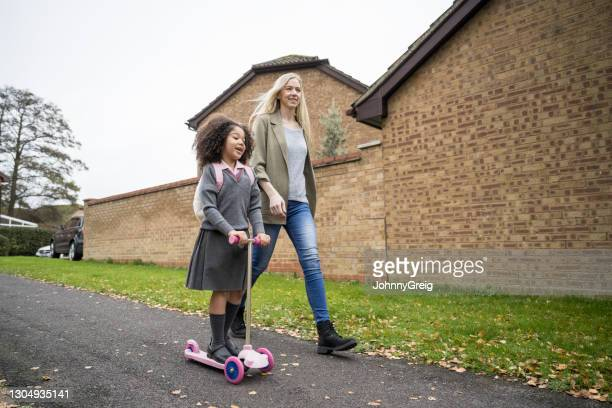 mother walking elementary age daughter to school - mid length hair stock pictures, royalty-free photos & images