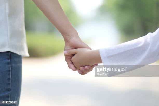 Mother walking hand in hand with her daughter