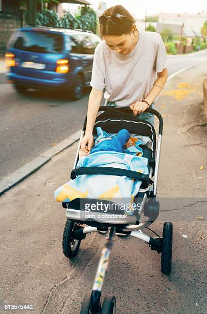 Mother walking with child in pram