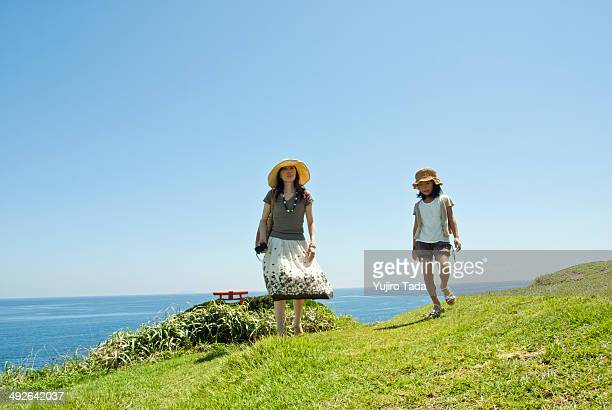 Mother walking with daughter at coastline