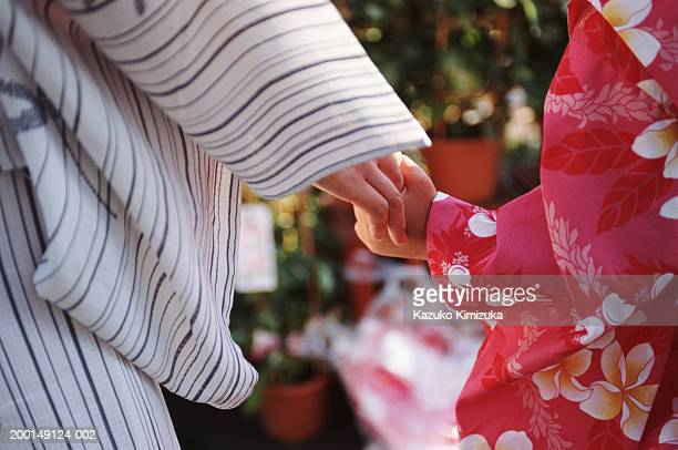 mother walking with daughter (5-7), close-up of hands - kazuko kimizuka ストックフォトと画像