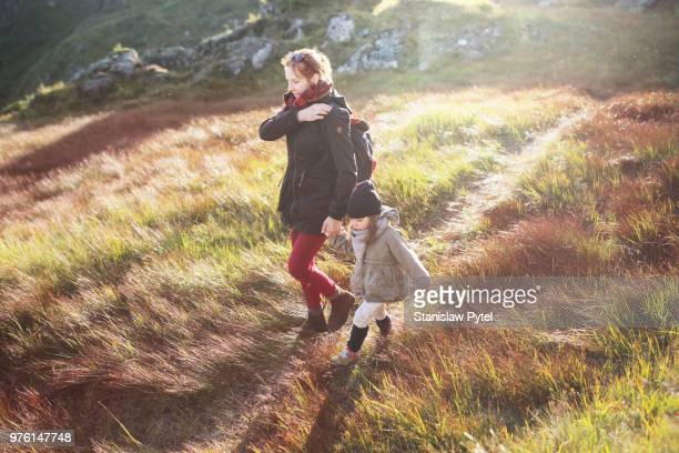 Mother walking with daughter in mountains on colorful grass