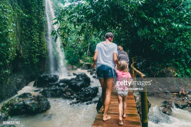 mother walking with   daughter  on bridge   near waterfall in bali, indonesia - family vacation stock pictures, royalty-free photos & images